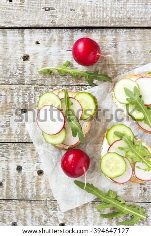 Bruschetta with cottage cheese, radish, cucumber and arugula.Top view - stock photo