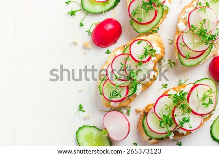 bruschetta with feta cheese, radish and cucumber on white background, top view, copy space - stock photo