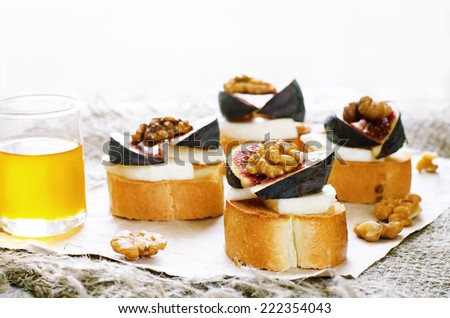 bruschetta with figs, honey, goat cheese and walnuts on a light background. tinting. selective focus on walnut - stock photo