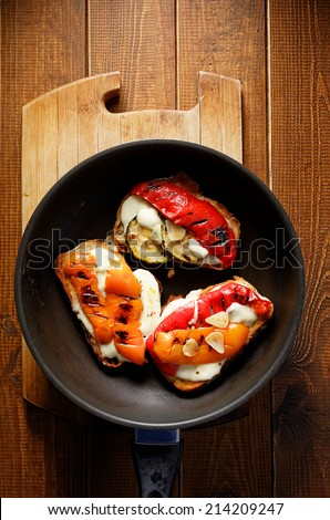 Bruschetta with grilled bell pepper, zucchini and mozzarella cheese. Vegetarian dish - stock photo