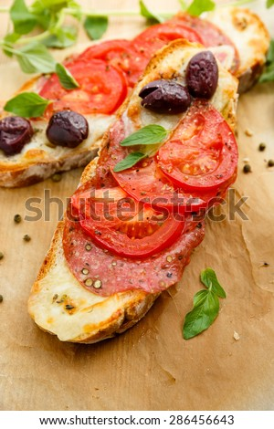 Bruschetta with mozzarella cheese, salami, tomatoes and kalamata olives - stock photo