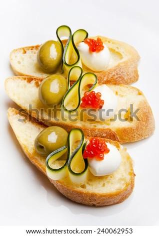 bruschetta with mozzarella, green olives, zucchini & red caviar - stock photo