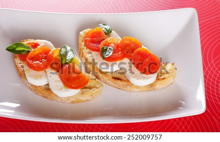 Bruschetta with mozzarella, tomatoes and olive oil  - stock photo