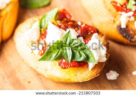Bruschetta with olive oil, sundried tomatoes, feta and fresh basil - stock photo