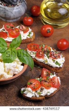 Bruschetta with ricotta and cherry tomatoes seasoned   spices, basil - stock photo