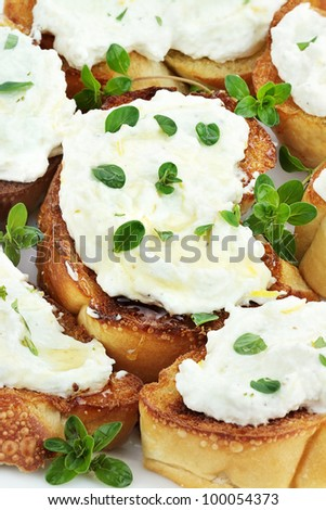 Bruschetta with ricotta cheese, lemon zest and thyme, drizzled with golden honey.  Shallow depth of field. - stock photo