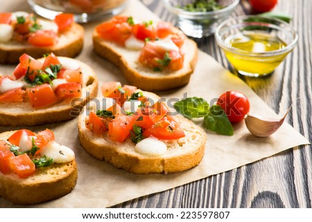 Bruschetta with roasted tomatoes, mozzarella cheese, garlic and basil - stock photo