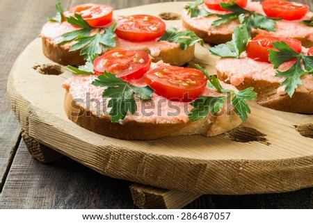 Bruschetta with salmon butter, capelin caviar, cherry tomatoes and parsley on an old wooden board in a rustic style. Selective focus - stock photo