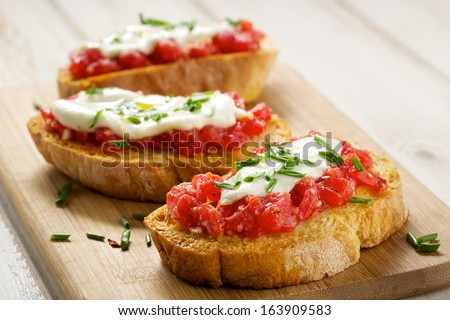 Bruschetta with tomato, mozarella and chive - stock photo