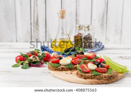bruschetta with tomato, olives and greenery on wooden table - stock photo