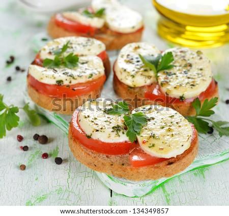 Bruschetta with tomatoes and mozzarella on a white table - stock photo