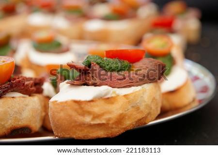 Bruschettas with beefsteak and pesto sauce - stock photo