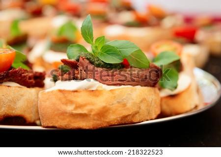 Bruschettas with beefsteak and pesto sauce, close-up - stock photo