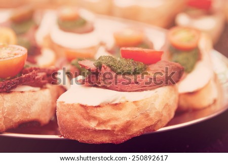 Bruschettas with beefsteak and pesto sauce, close-up, toned image - stock photo