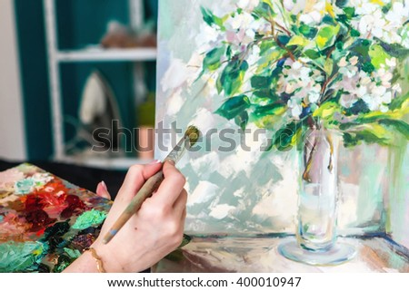 Brush and oil paints on a palette, paint a picture of the artist's hands, texture mix paint in different colors. Artist holding a palette with paint, brushes and palette knife - stock photo