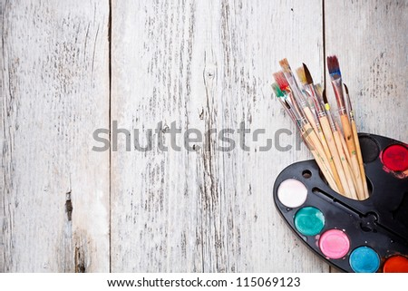 Brush and paints on old wood background - stock photo