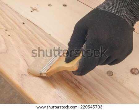 Brush finishing by hand on pine wood. - stock photo