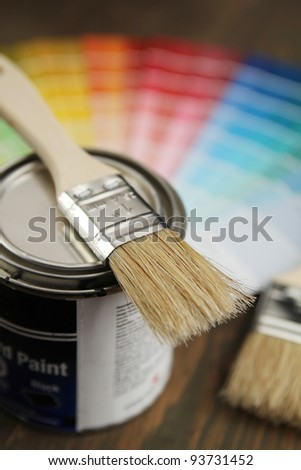 Brush on a little bucket with a color guide in background - stock photo
