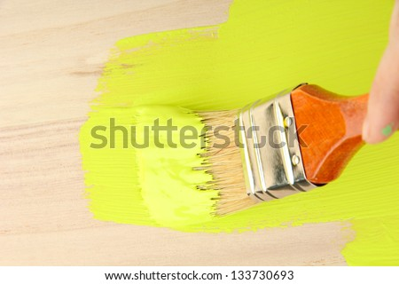 Brush painting wooden furniture, close up - stock photo