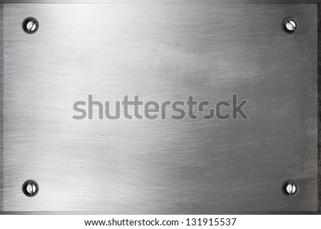 Brushed silver metal surface with bolts - stock photo
