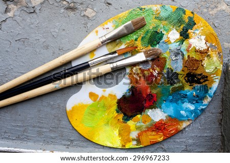 Brushes and colorful abstract oil colors painters pallet, on retro background - stock photo