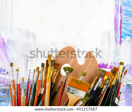 Brushes with a palette  on a creative background - stock photo