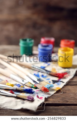 Brushes with colorful paints on old wooden background - stock photo