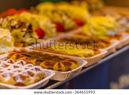 BRUSSELS, BELGIUM - 11 AUGUST, 2015: Famous belgian waffles as displayed in store with cream, berries and chocolate sauce - stock photo