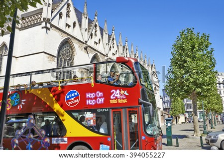 BRUSSELS, BELGIUM - AUGUST 29, 2015: Some people enjoy visiting Brussels with the World famous red sightseeing bus for tourists on the Notre-Dame de la Chapelle square in brussels - stock photo