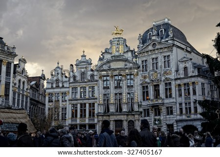 BRUSSELS, BELGIUM-DECEMBER 6, 2014: Crowded by tourists Grand Place of Brussels with installed Christmas Tree, decorated with symbols of Riga, capital of Latvia - stock photo