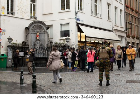 BRUSSELS, BELGIUM - DECEMBER 1: Touristic area hosting the famous statue of Manneken Pis being guarded by a Belgian soldier due to security alert . December 1, 2015 in Brussels, Belgium. - stock photo