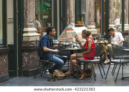 BRUSSELS, BELGIUM - JULY 4, 2015: A couple eating an ice cream at a cafe in the Galeries Royales Saint Hubert, in the city center, the first commercial galleries of Europe. - stock photo