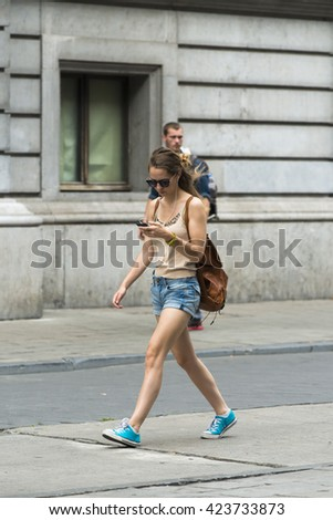 BRUSSELS, BELGIUM - JULY 4, 2015: A young woman consults her Smartphone, while walking down one of the streets of the city. - stock photo