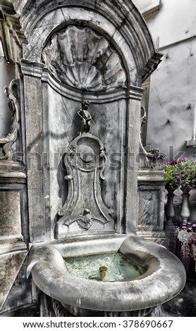 BRUSSELS, BELGIUM - JULY 10, 2015: Manneken Pis statue, one of the most famous Belgian and Brussels monuments and a symbol of the city - stock photo