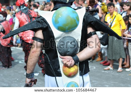 BRUSSELS, BELGIUM-MAY 19: An unknown participant demonstrates his creative globe costume during Zinneke Parade on May 19, 2012 in Brussels. This parade is biennial urban artistic free-attendance event - stock photo