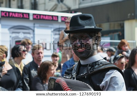 BRUSSELS, BELGIUM-MAY 19: An unknown participant with colored face plays music during Zinneke Parade on May 19, 2012 in Brussels. This parade is a biennial free-attendance and attracted many tourists. - stock photo