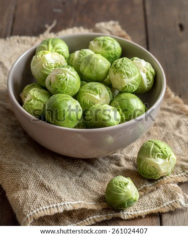 Brussels sprouts in a bowl on burlap on a wooden table - stock photo