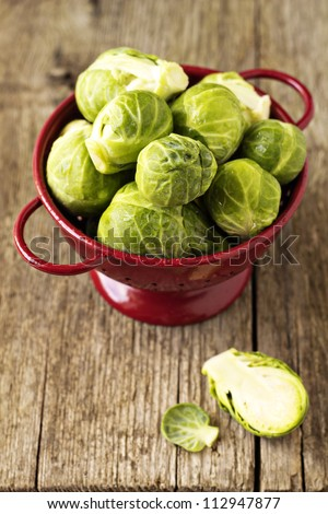 Brussels sprouts in a red colander - stock photo