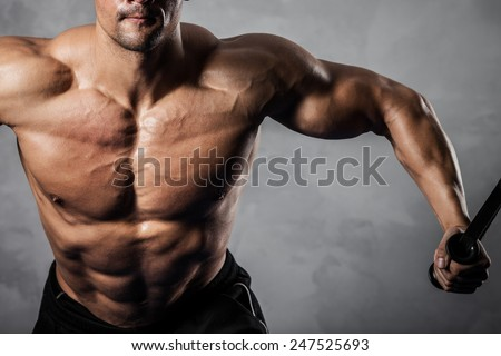 Brutal athletic man pumping up muscles on crossover - stock photo