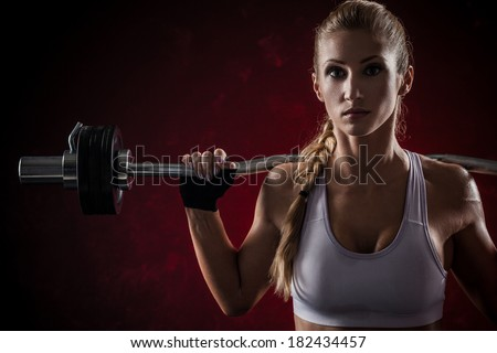 Brutal athletic woman pumping up muscles with barbell on red background - stock photo