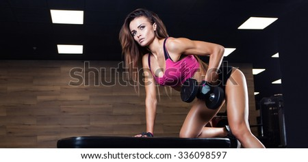 Brutal athletic woman pumping up muscles with dumbbells  - stock photo