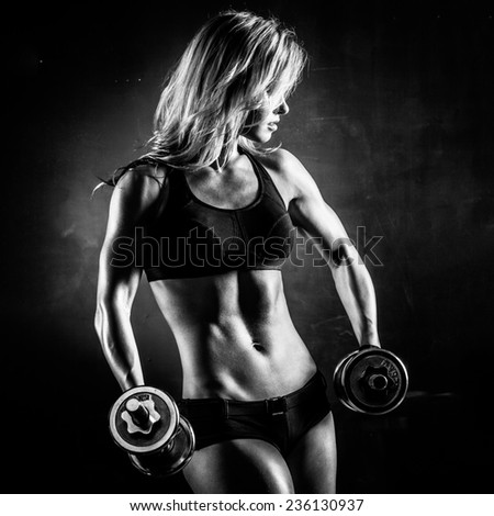 Brutal athletic woman pumping up muscles with dumbbells in monochrome - stock photo