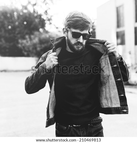Brutal black and white portrait of a fashionable man with a beard and glasses - stock photo