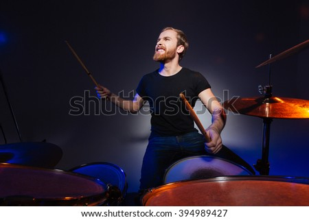Brutal excited young man drummer with beard playing drums over dark background - stock photo