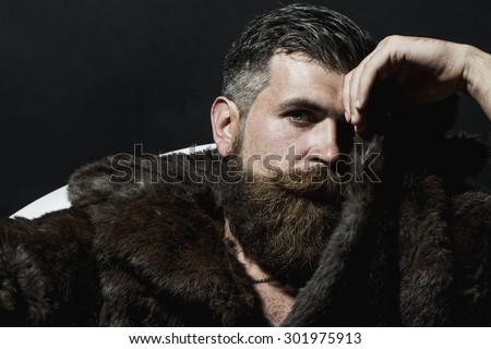 Brutal handsome sullen unshaven man with long beard and moustache in brown fur coat with collar sitting in white bath tub on black background copyspace, horizontal picture - stock photo