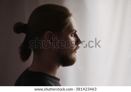 brutal man in profile with a mustache and a beard with long hair gathered in a tail with natural light - stock photo