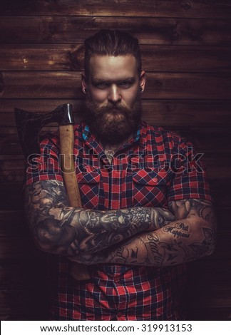Brutal man with beard and tattooe holding axe over wooden wall. - stock photo