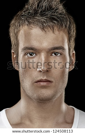 Brutal portrait of young man close up on black background. - stock photo