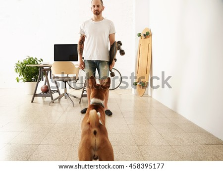 Brutal tattoooed man in blank t-shirt holds surf skateboard in huge room in front of his working desktop with computer while his basenji dog looks at him Vintage bike parked on back. - stock photo
