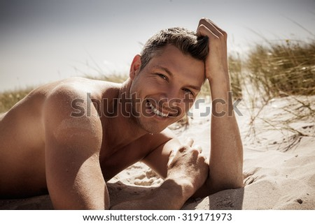brwoning tanned male on the sea - stock photo